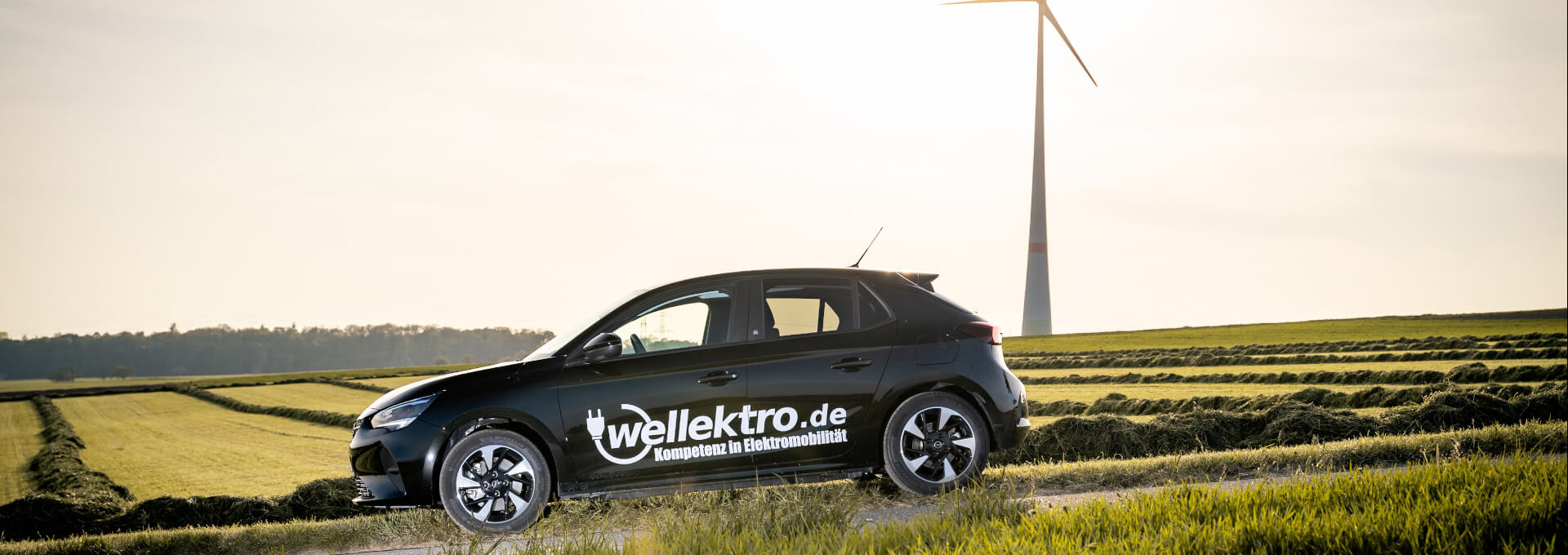 schwarzer Corsa Elektro vor Windrad